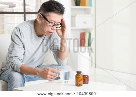 Portrait of 50s mature Asian man headache, pressing on head with painful expression, sitting on sofa at home, medicines and water on table.