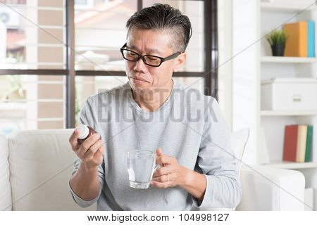 Men health concept. Portrait of 50s mature Asian man reading the label on bottle medicine, sitting on sofa at home.