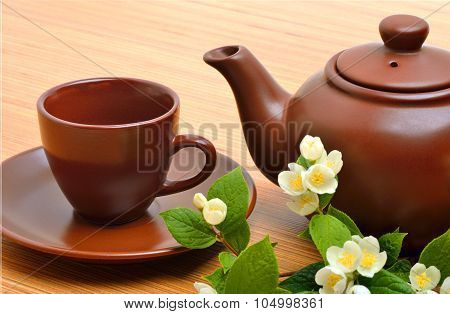 Teapot, Teacup, Saucer And Jasmine Flower Twig On Wood