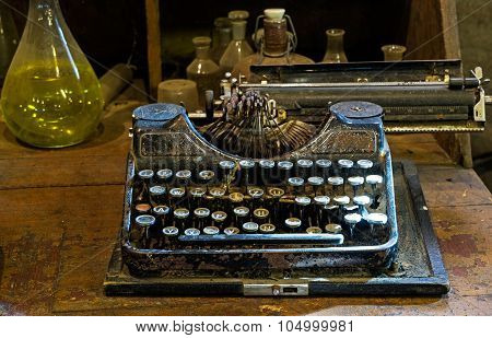 The Old Typewriter On A Dusty Table With Bottles