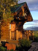 foto of log cabin  - Entryway to a log house with mountains in the background - JPG