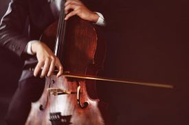 pic of cello  - Man playing on cello on dark background - JPG