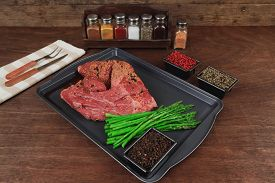 foto of peppercorns  - meat raw beef fillet chunk on black tray asparagus on wooden table allspice pink white black green peppercorn stainless cutlery knife fork - JPG