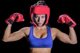 pic of headgear  - Portrait of female fighter with gloves and headgear against black background - JPG
