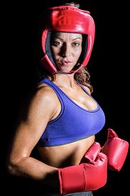 stock photo of headgear  - Portrait of pretty boxer with headgear and gloves against black background - JPG