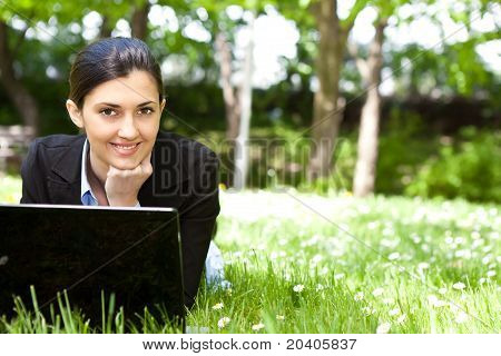 Young Woman Working On Laptop In The Field
