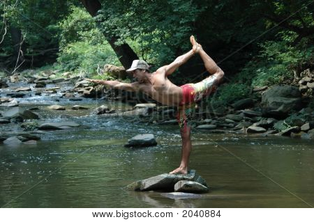 Triange Yoga Pose On A Rock In A Creek
