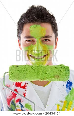 Male painter with a roller brush and paint on his face  - isolated