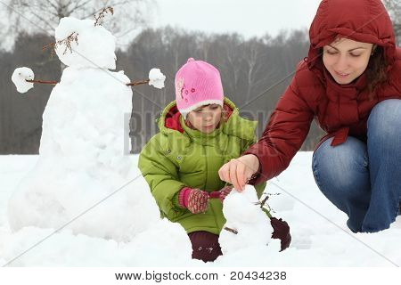 Mother and girl in winter on outdoor sculp little snowman