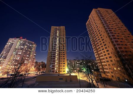 Dwelling district with skyscraper in evening in winter