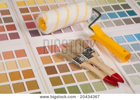 Brushes and a paint roller on color palette