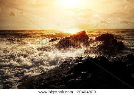 Strong sea waves breaking on coast rocks with splashes