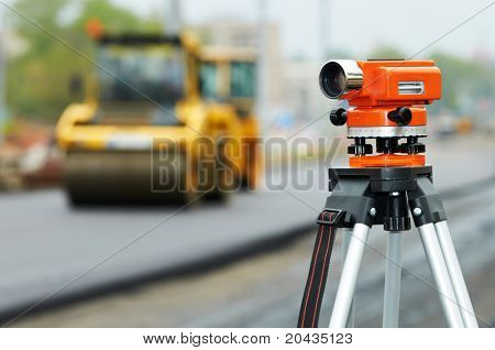 Construction surveyor equipment theodolite level tool during asphalt paving works with compactor roller at background