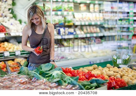 Beautiful young woman shopping for fruits and vegetables in produce department of a grocery store/supermarket