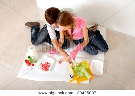 Young couple preparing paints while sitting on floor in new flat