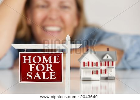 Smiling Woman Leaning on Hands Behind Home For Sale Real Estate Sign and Model House on a White Surface.
