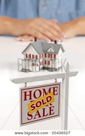 Woman's Folded Hands Behind Model House and Sold Home For Sale Real Estate Sign In Front on White Surface.