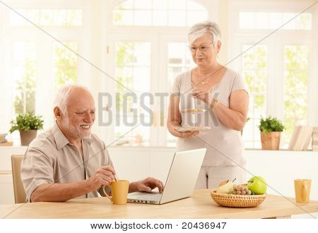 Happy senior man using laptop computer and having coffee at kitchen table, wife serving cookies.?
