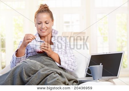 Young female having breakfast at home, dieting, eating yoghurt in bed, using laptop.?