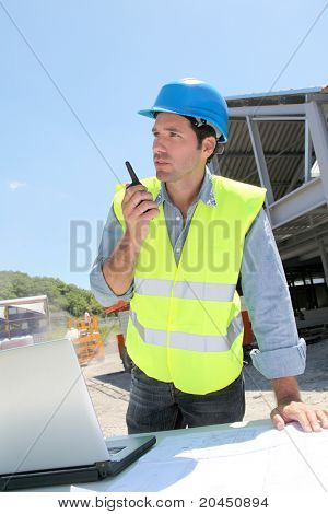 Foreman using walkie-talkie on construction site