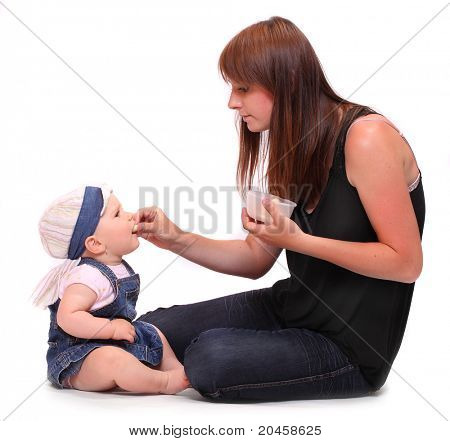 Young mother feeds her baby. Studio shot on a white background.