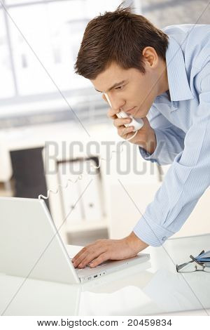 Young office worker man speaking on landline phone using laptop computer, looking at screen.?