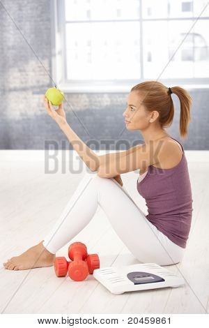 Sporty young woman posing with green apple in gym, sitting with scale and dumbbells.?