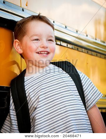 Happy young boy in front of yellow school bus waiting to board on first day back to school.
