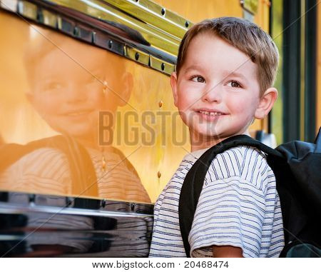Young boy with nervous smile waits to board bus on first day of school.
