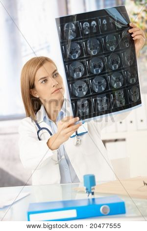 Young attractive female doctor sitting at desk, studying x-ray image.?