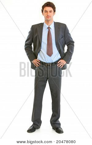 Full length portrait of modern young businessman with hands on hips isolated on white