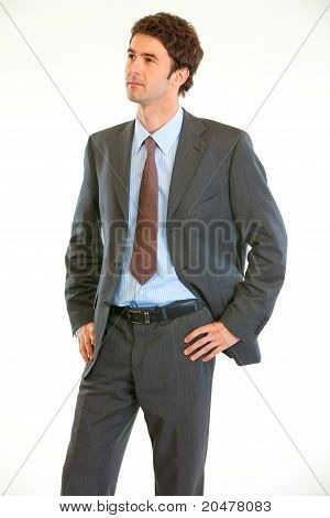 Confident modern businessman with hands on hips looking in corner at copy-space