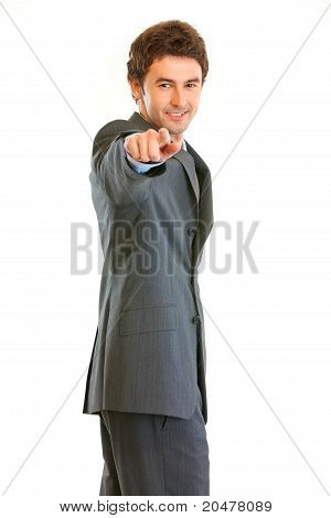 Smiling modern businessman pointing finger at you isolated on white