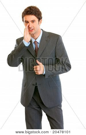 Smiling modern businessman reporting good news and showing thumbs up gesture isolated on white
