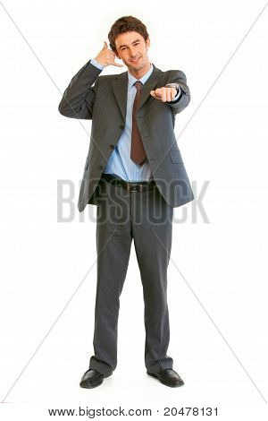 Full length portrait of smiling businessman showing contact me gesture isolated on white