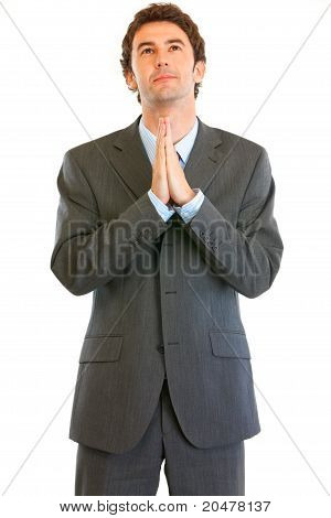 Young businessman praying for success isolated on white
