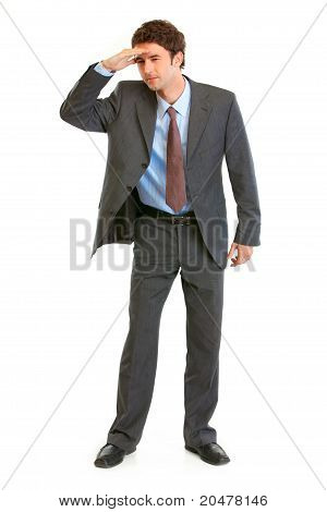 Concentrated young businessman holding his hand at forehead and looking forward in future isolated