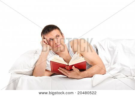 A young thoughtful man with a book lying on his bed isolated on white background