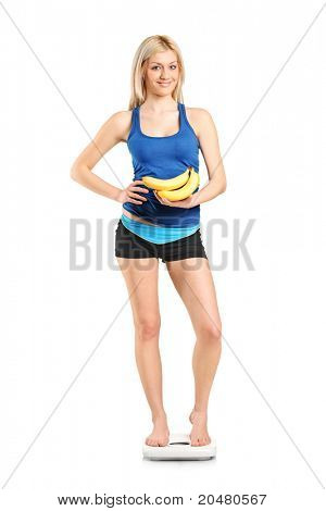 Full length portrait of a female athlete on a weight scale holding bananas isolated on white background