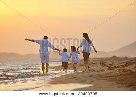 glücklich junge Familie viel Spaß am Strand laufen und springen bei Sonnenuntergang