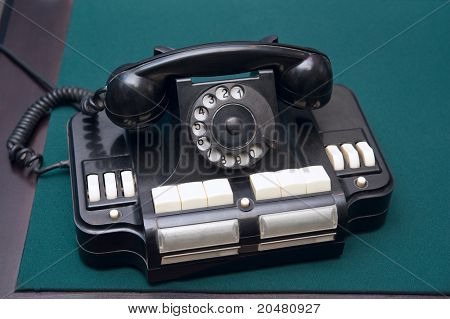 Old black telephone on a table surface