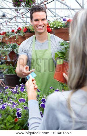 Joven sonriente a floristas vendedor trabajando en florería.