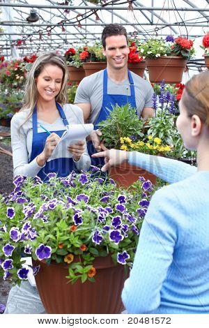 Floreria de vendedor sonriente joven trabajando en florería.