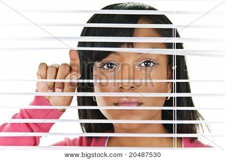 Woman Looking Through Venetian Blinds