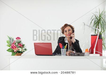 Empresaria habla por teléfono.
