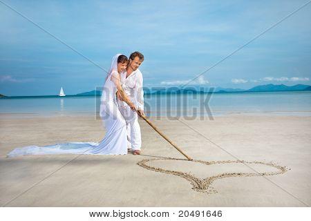 beautiful couple on the beach in wedding dress drawing heart