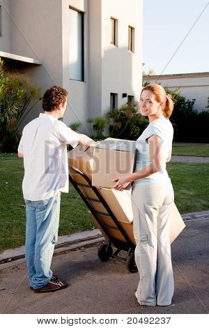 A happy moving couple with boxes on a trolly