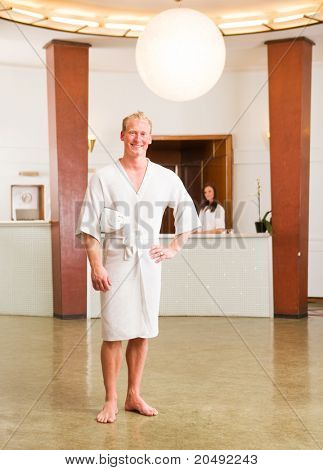A man in a bathrobe standing in a reception of a spa, looking at the camera