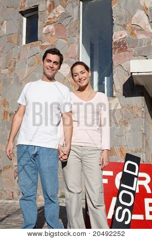 Happy young couple in front of their new home with sold sign in background