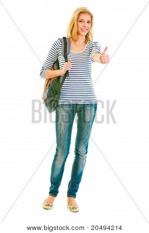 Full length portrait of smiling teen girl with schoolbag showing thumbs up gesture isolated on white